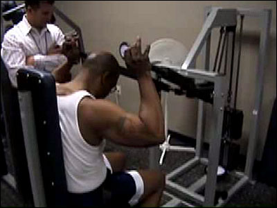 Bo Railey trains Vee Ferguson on the SuperSlow Systems overhead press machine