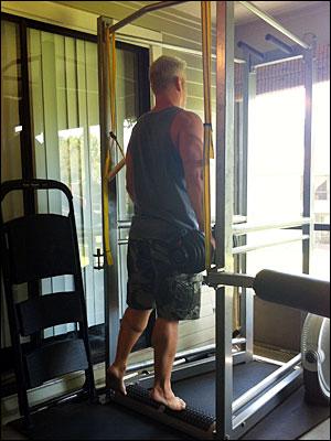 One-legged dumbbell heel raises on the UXS bodyweight multi-exercise station
