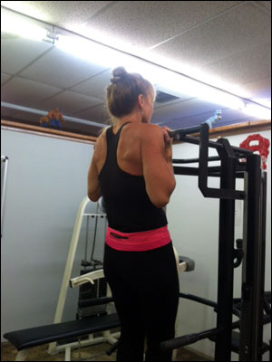 A 52  year old client of Doug Hollands performing chin-ups at the end of her workout
